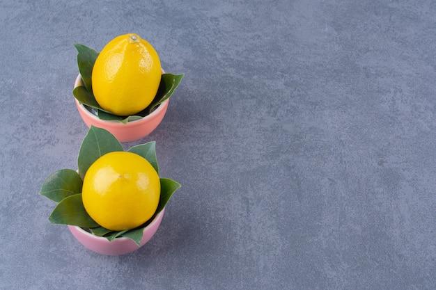 Две миски спелых лимонов с листьями, на темной поверхности