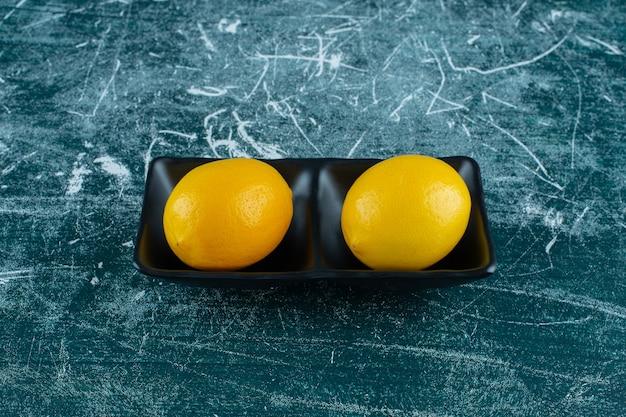 Две чаши спелых лимонов с листьями на мраморном фоне. фото высокого качества