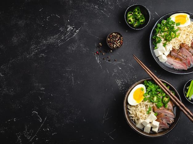 검은색 소박한 돌 배경에 국물, 두부, 돼지고기, 계란을 넣은 맛있는 아시아 누들 수프 라면 두 그릇, 문자를 위한 공간, 클로즈업, 위쪽 전망. 복사 공간이 있는 저녁 식사로 뜨거운 맛있는 일본 라면 수프
