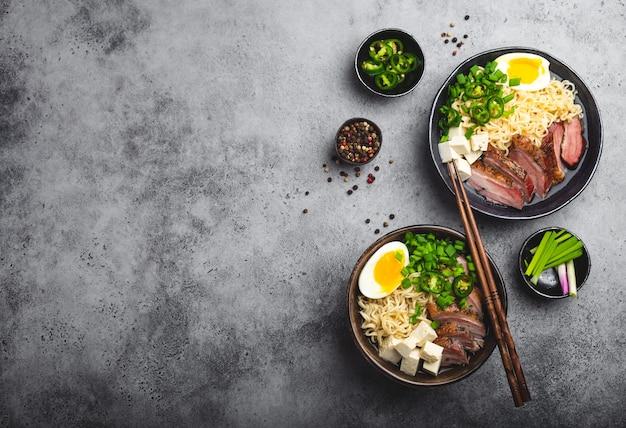 회색 소박한 콘크리트 배경에 국물, 두부, 돼지고기, 계란을 넣은 맛있는 아시아 누들 수프 라면 두 그릇, 문자 공간, 클로즈업, 위쪽 전망. 복사 공간이 있는 저녁 식사로 뜨거운 맛있는 일본 라면 수프