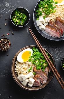 검은색 소박한 콘크리트 배경에 고기 국물, 두부, 돼지고기, 달걀 노른자가 있는 맛있는 아시아 누들 수프 라면 두 그릇이 닫혀 있습니다. 저녁 식사 아시아 스타일을 위한 뜨거운 맛있는 일본 라면 수프
