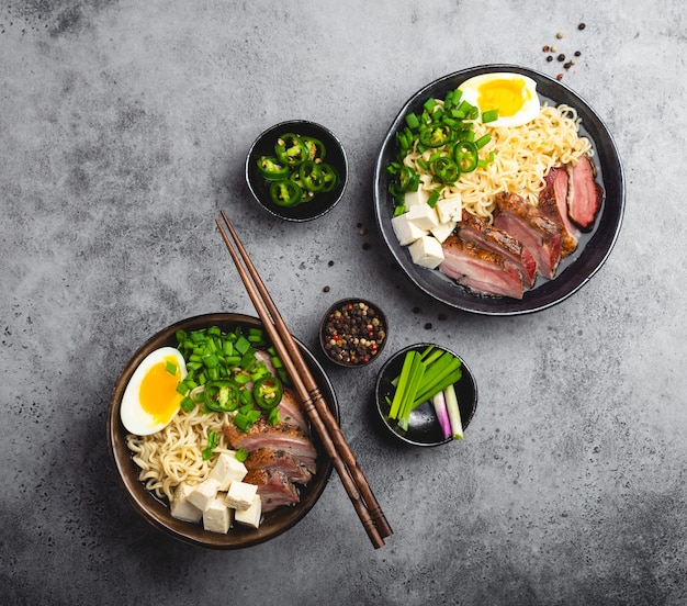 회색 소박한 콘크리트 배경에 고기 국물, 두부, 돼지고기, 달걀 노른자가 있는 맛있는 아시아 누들 수프 라면 두 그릇이 닫혀 있습니다. 저녁 식사 아시아 스타일을 위한 뜨거운 맛있는 일본 라면 수프