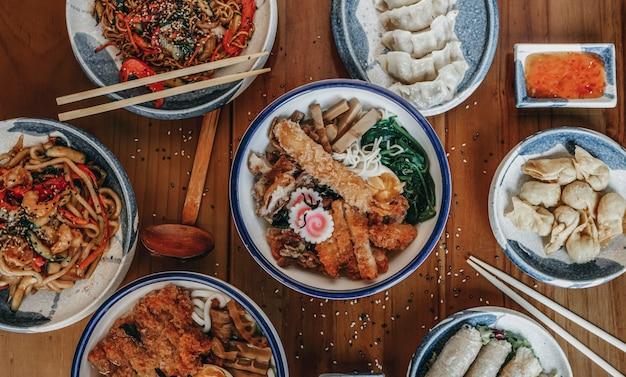 쇠고기 국물, 닭고기, 나무 표면에 노른자위가있는 계란과 함께 맛있는 아시아라면 국수 수프 두 그릇을 닫습니다.
