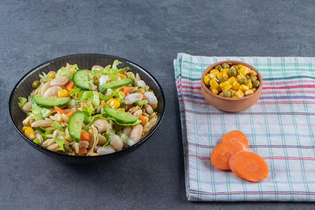 Две миски овощного салата и нарезанной моркови на кухонном полотенце на мраморной поверхности