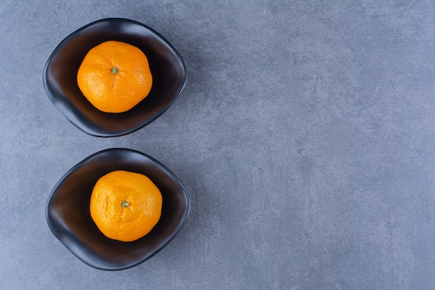 Two bowls of oranges, on the dark surface