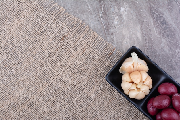 Two bowls of pickled garlic and plums on burlap.