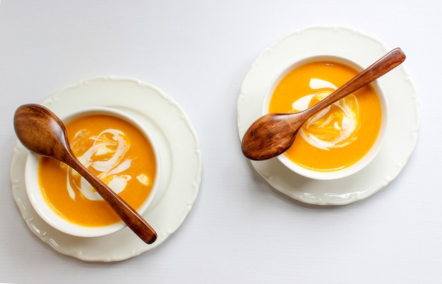 Two bowls of pumpkin soup on white background with gray fabric and slices of butternut squash