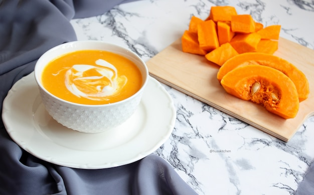 Two bowls of pumpkin soup with gray fabric and slices of butternut squash, top view, vegetarian food
