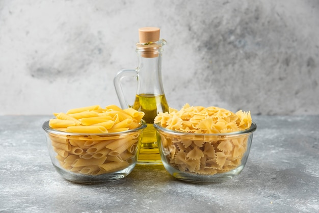 Two bowls of raw penne and farfalle pasta with bottle of olive oil on marble surface.