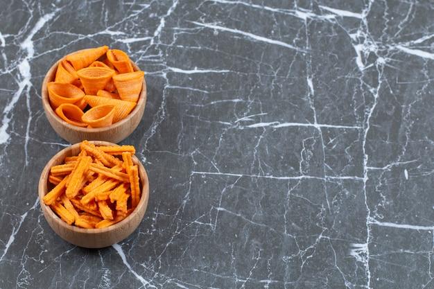 Due ciotole di stick e chips triangolari su marmo.
