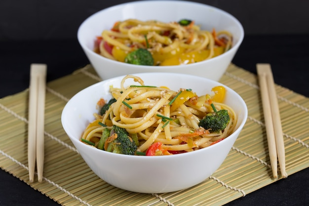 Two bowls of stir fry noodles with vegetables and soy sauce on a bamboo mat