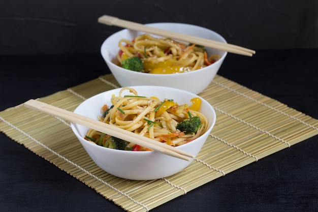 Two bowls of stir fry udon noodles with vegetables and soy sauce on a bamboo mat