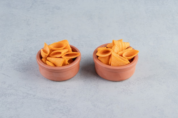 Two bowls of triangle shaped crispy chips on stone background.