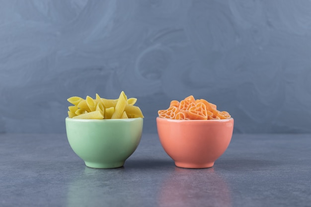 Two bowls of various pasta on stone background.