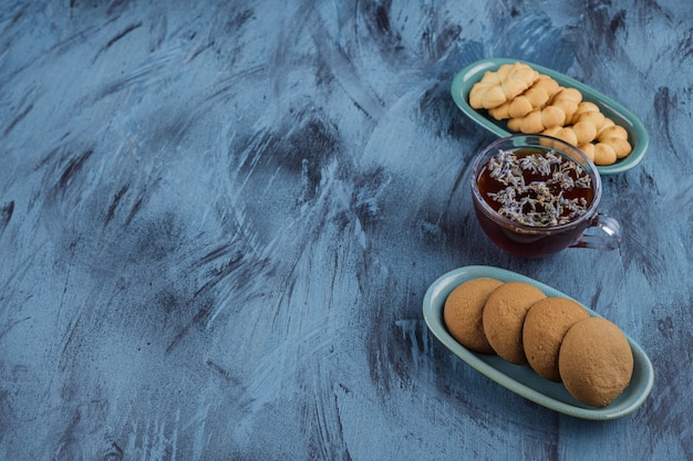 Two bowls of various sweet biscuits and black tea on blue background.