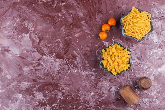 Две миски с разными видами сырых сухих макарон и желтых помидоров черри на светлом столе.