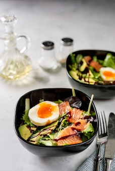 Two bowls with salad, egg and salmon for breakfast