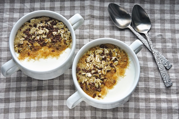 Two bowls with white yogurt, bran and seeds. healthy breakfast. diet food.
