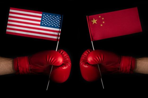 アメリカと中国の旗を持つ2つのボクサーの手