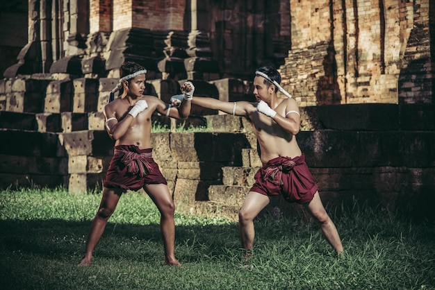 Two boxers fight with the martial arts of muay thai.