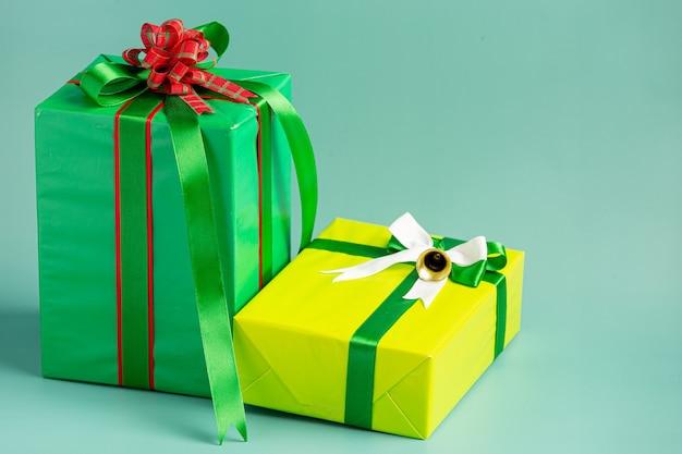 薄緑色の背景に弓でプレゼントの2つのボックス