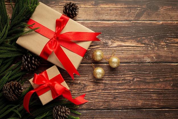 木製の背景に赤いリボンの弓とプレゼントの2箱