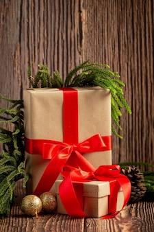 Две коробки подарков с бантом из красной ленты на деревянном фоне