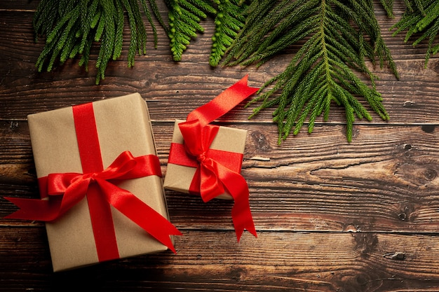 Two boxes of present with red ribbon bow on wooden background