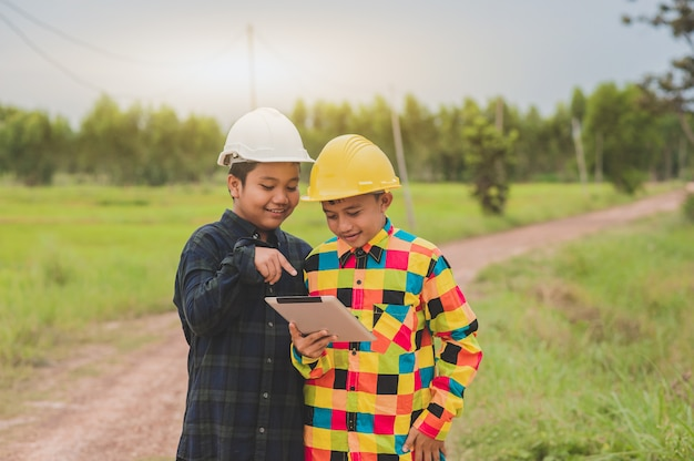 2人の少年アジアの人々は目立つタブレット、コンセプトエンジニアまたはフォアマン建設管理、教育コラージュ研究学校を使用してハード帽子をかぶっています。