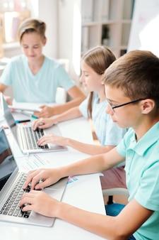Два мальчика и девочка в повседневной одежде сидят за столом перед ноутбуками во время финального экзамена в классе