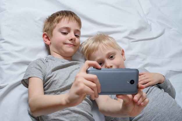 Two boys are lying in bed with a smartphone. gadget leisure