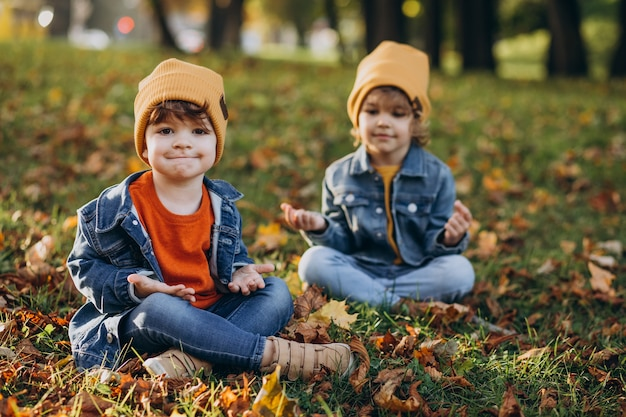 Два брата мальчика занимаются йогой в парке