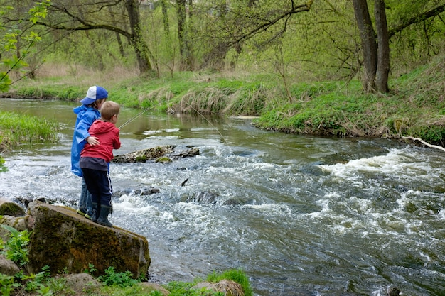 Two boys brothers, dressed in red and blue raincoat, are fishing together on the mount river