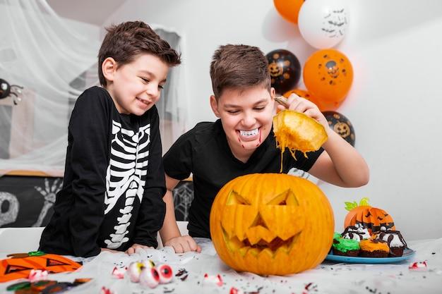 Два мальчика, братья в костюмах, смотрят, что внутри тыквы jack o 'lantern на хэллоуин на столе. счастливого хэллоуина