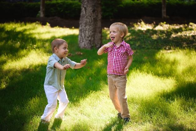 公園で野外で遊んだりジャンプしたりする2人の男の子の兄弟。