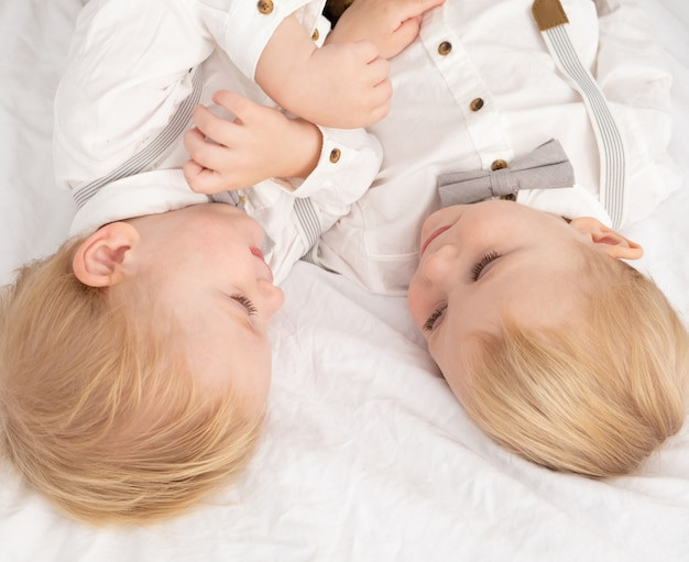 Two boys brothers twins in white shirts looking at each other.