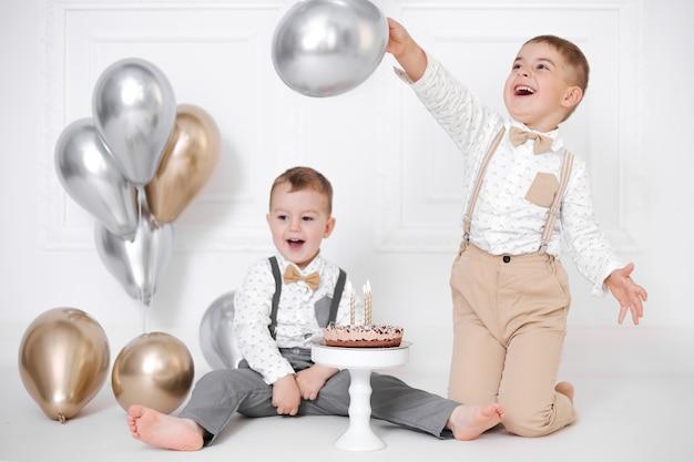 誕生日を祝う2人の男の子、子供たちはb-dayパーティーをします。キャンドルと風船のバースデーケーキ。幸せな子供たち、お祝い、白いミニマリストのインテリア。