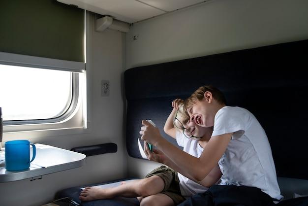 二人の少年がコンパートメントの馬車に乗って騙されます。鉄道車両の子供たち。若い乗客のための娯楽。