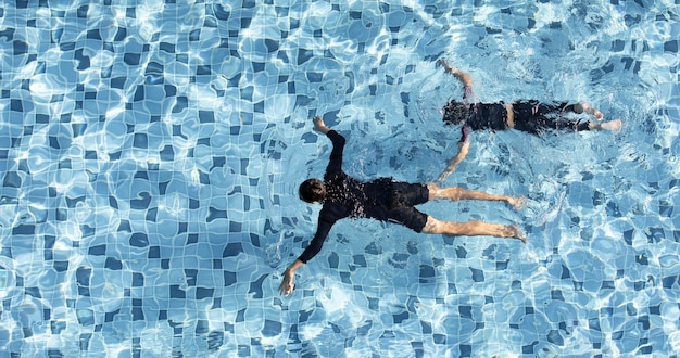 Two boys funny swimming together in clear water pool, taken from aerial view.