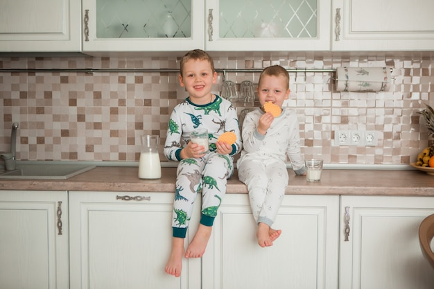 Two boys have breakfast in the kitchen