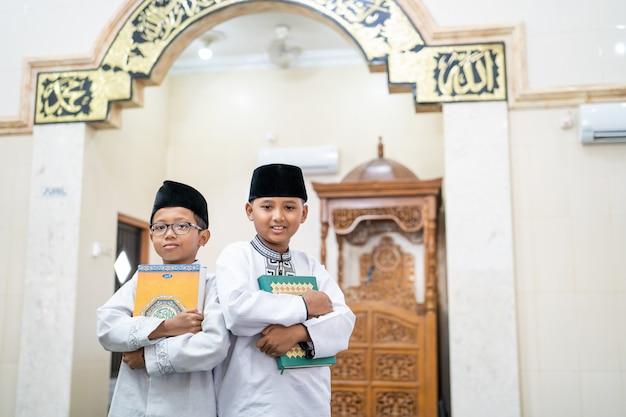 聖なるコーランを保持している2人の男の子