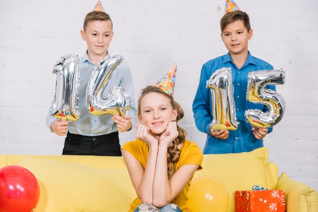 Two boys holding numeral 14 and 15 foil balloons in hand standing behind the birthday girl