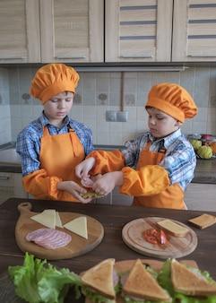 オレンジ色の衣装を着た2人の男の子が、キッチンでハム、チーズ、トマトのサンドイッチを調理します