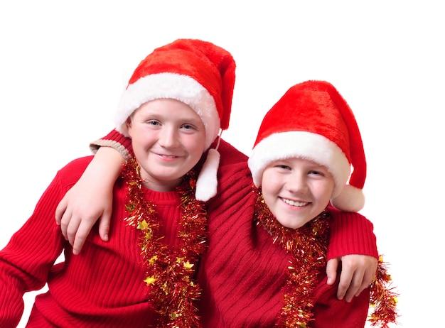 白で隔離赤いサンタ帽子の2人の男の子