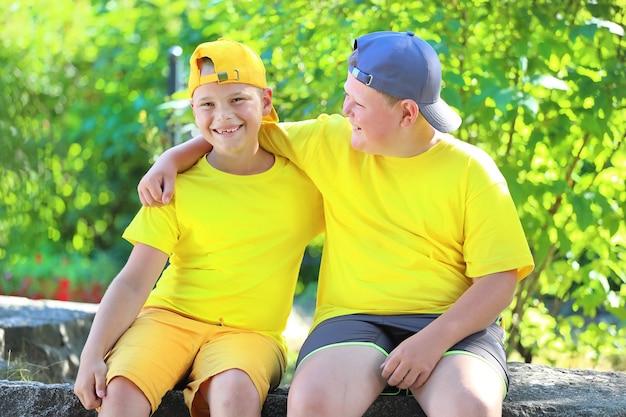 공원에 앉아 껴안고 있는 노란색 티셔츠를 입은 두 소년. 고품질 사진
