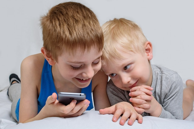 Two boys lie in bed and look at the smartphone. gadget leisure