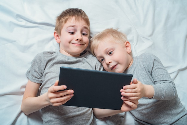 Two boys lying in bed and watching something on a tablet. gadget leisure