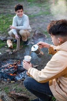 Два мальчика варят кофе с помощью кофеварки на пикнике, перед ними костер