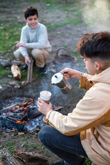 Two boys making coffee using a maker on a picnic, campfire in front of them