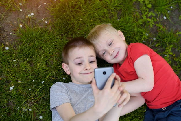 Two boys making a selfie with a smartphone lying on the grass.